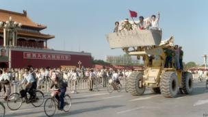 Workers sit in a bulldozer shovel, shouting slogans as they drive their engine in front of the Forbidden City in Tiananmen Square on 25 May 1989