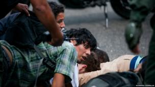 An anti-government demonstrator is held on the ground along with others, as he is detained by the Bolivarian National Guard