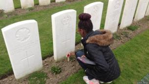School Reporter Charlotte lays a cross on a World War One grave