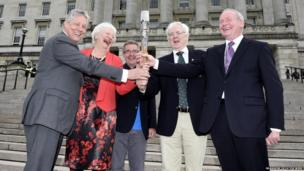 Peter Robinson, Olympic champion Mary Peters, Chris Jenkins, Robert McVeigh and Martin McGuinness hold the Queen's baton on the steps of Stormont, Belfast, Northern Ireland