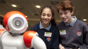 Fatemah and Cerys watch as the robot dances