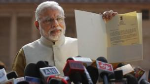 "In this Tuesday, May 20, 2014 file photo, India""s Prime Minister-elect Narendra Modi displays the letter from the Indian president inviting him to form the new government"