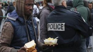 An Eritrean migrant walks past a police officer during the daily food distribution at the harbour in Calais