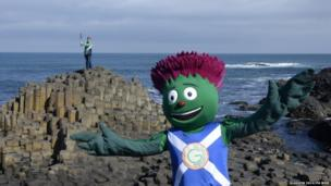 Woman standing on a coastal hexagonal rock formation holds Queen's Baton aloft while a person dressed as a cartoon thistle waves in the foreground.