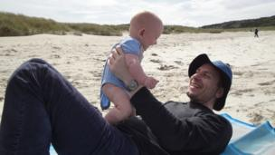Father and baby on beach