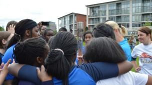 A group of girls gather around the Queen's Relay Baton