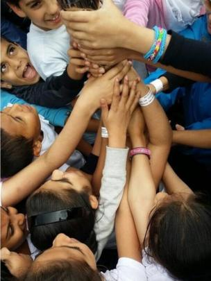 Children with their hand on the baton in Ward End Park