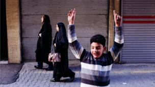 A boy celebrates scoring a goal during an impromptu football match in a street in Tehran