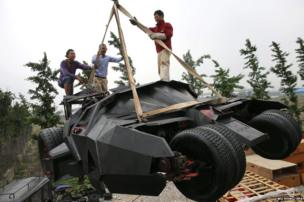 Li Weilei (centre) and two mechanics lift a replica of the Batmobile at a workshop in Shanghai