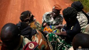 Seleka fighters carry a sick child to her mother, at a village between Bambari and Grimari