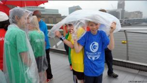 Lambeth school children take shelter from the rain on the Millennium Bridge