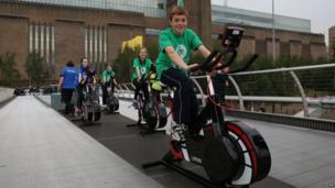 Lambeth school children ride static bikes on the Millennium Bridge