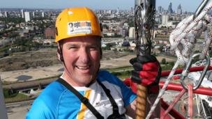 Sir Matthew Pinsent CBE holds the Queens Baton as he abseils down the Orbit tower at the Queen Elizabeth Olympic Park