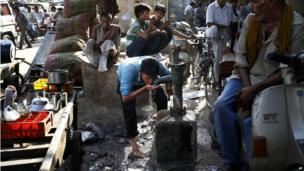 An Indian day labourer quenches his thirst from a roadside tube well in Delhi.