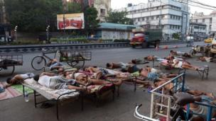 Daily labourers and rickshaw van pullers sleep on a roadside in an attempt to stay cool from overnight heat, at dawn in Kolkata