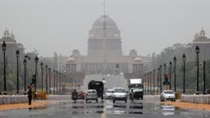Commuters travel through a mirage on a hot summer day in front of India's presidential palace in Delhi