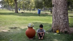 A boy sells lemon water in an earthen pot in a public park in Delhi.