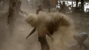 Locals throw dry soil at each other before a dip to cool off in a canal on a hot day in Lahore. 8 June 2014