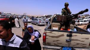 Iraqi families fleeing violence in the northern Nineveh province gather at a checkpoint about 40km west of Erbil, on 10 June 2014