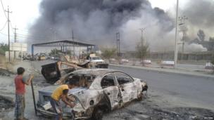 Civilian children stand next to a burnt vehicle during clashes between Iraqi security forces and al Qaeda-linked Islamic State in Iraq and the Levant (ISIS) in the northern Iraq city of Mosul, 10 June 2014