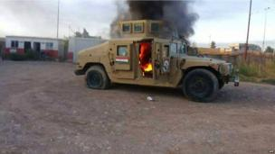 A picture taken with a mobile phone shows an armoured vehicle belonging to Iraqi security forces in flames on 10 June 2014, after hundreds of militants from the Islamic State of Iraq and the Levant (ISIS) launched a major assault on the security forces in Mosul