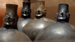 Black ceramic bottles with humanoid faces and necks, are displayed at the Art Museum of Lima