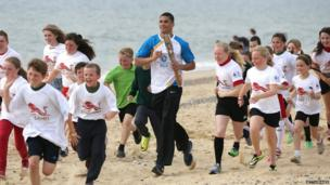 Olympic boxer Anthony Ogogo carries the Queen's Baton along the Lowestoft Seafront on 8 June 2014 in Suffolk