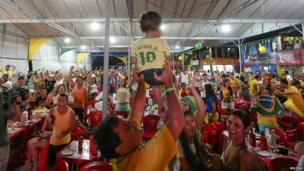 Brazilian soccer fans celebrate the third goal of their team against Croatia as they watch the opening match of the FIFA Brazil 2014 World Cup in a beach restaurant in Porto Seguro (12 June 2014)