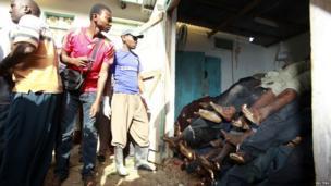 Residents look at slain slain bodies of people killed when unidentified gunmen attacked the coastal Kenyan town of Mpeketoni