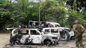Wreckages of burnt cars are seen outside Mpeketoni police station after unidentified gunmen attacked coastal Kenyan town of Mpeketoni