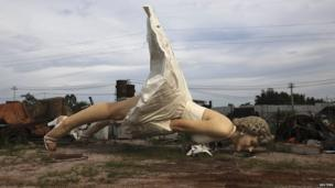Giant statue of actress Marilyn Monroe at rubbish collection site in Guigang, China. 18 June 2014
