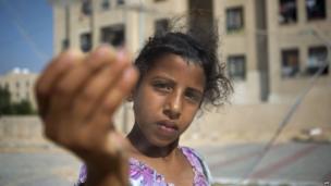 Palestinian girl displays broken glass following Israeli air strike in Gaza Strip. 19 June 2014