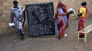 South Sudanese women with a chalkboard at a camp on the outskirts of Khartoum, on 16 June 2014
