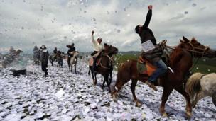 Tibetans throw praying papers while on horseback