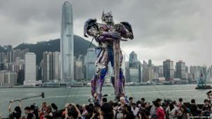 A statue of Optimus Prime figure is surrounded by journalists in Hong Kong