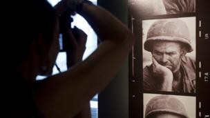 A woman looks at an image as she visits an exhibition of photographs by French photographer Gilles Caron