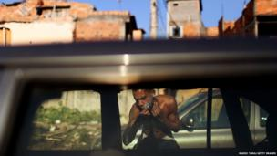 A resident shaves using a car window as a mirror amongst cars parked by World Cup tourists