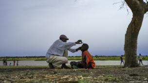 A father cuts his sons hair in Melut on the banks of the River Nile, South Sudan
