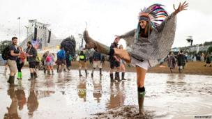 A woman kicks water in a puddle as she poses for photographers, on the first official day of the Glastonbury Festival