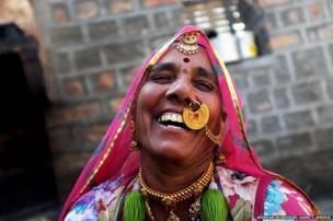 Sayeri devi in a light mood at her home wearing gold ornaments. Bisnois known to have affection for gold and it is also their status symbol as well as their investment. The design of the nose ring Sayari devi is wearing is a mark of being bishnoi. Jodhpur, Rajasthan, India.