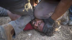 Israeli policemen and immigration officers arrest an African asylum seeker in the Negev Desert on 29 June 2014
