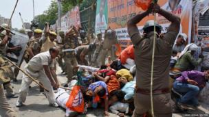 Indian policemen use batons to disperse youth wing workers of India's ruling Bharatiya Janata Party (BJP) during a protest outside the state assembly in the city of Lucknow