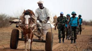 A farmer in Karbab riding his cart with UN troops on seen behind him on a routine patrol, South Darfur, Sudan - Tuesday 1 July 2014