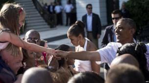 US First Lady Michelle Obama and US President Barack Obama greet guests on the South Lawn of the White House. 4 July 2014