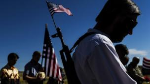 "Gun rights advocates pray at an ""open carry"" demonstration during the Independence Day parade in Westcliffe, Colorado. 4 July 2014"