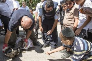 Israeli bomb disposal experts pick up the remains of a rocket, said to be fired by Palestinian militants, from outside a house in the southern Israeli city of Netivot. 10 July 2014.