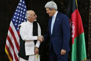 US Secretary of State John Kerry shakes hands with Ashraf Ghani