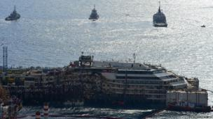 A general view shows tug boats near the wreck of the Costa Concordia