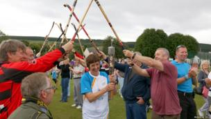 Woman carries baton under an archway formed from crossed shinty sticks