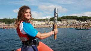 Tristan Levie holds Queen's baton aloft at prow of boat approaching a crowd-lined shore